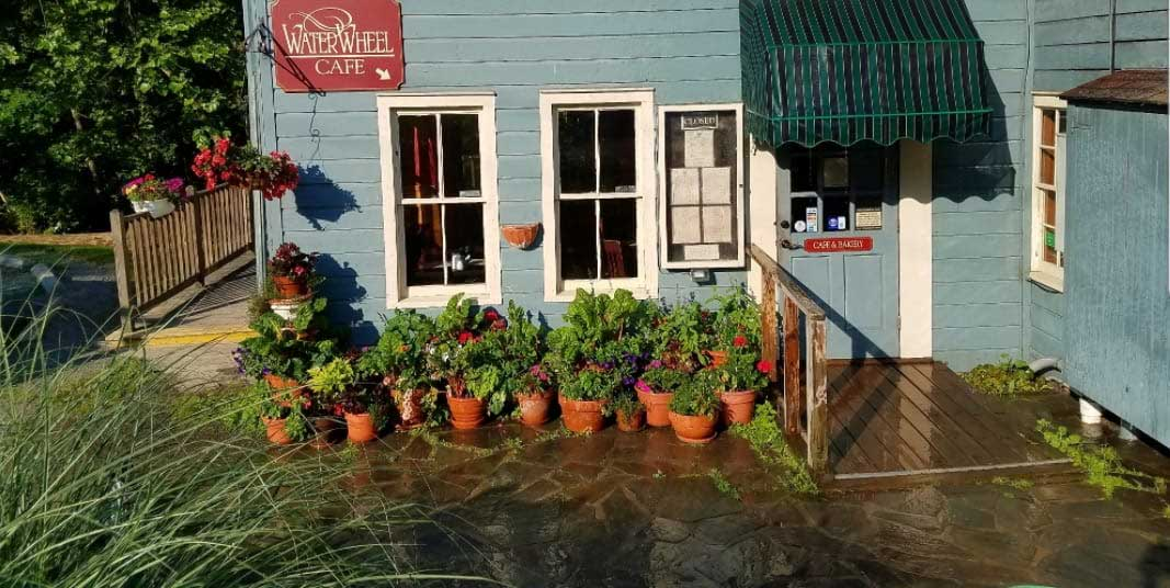 the outside entrance of the waterwheel cafe and potted plants