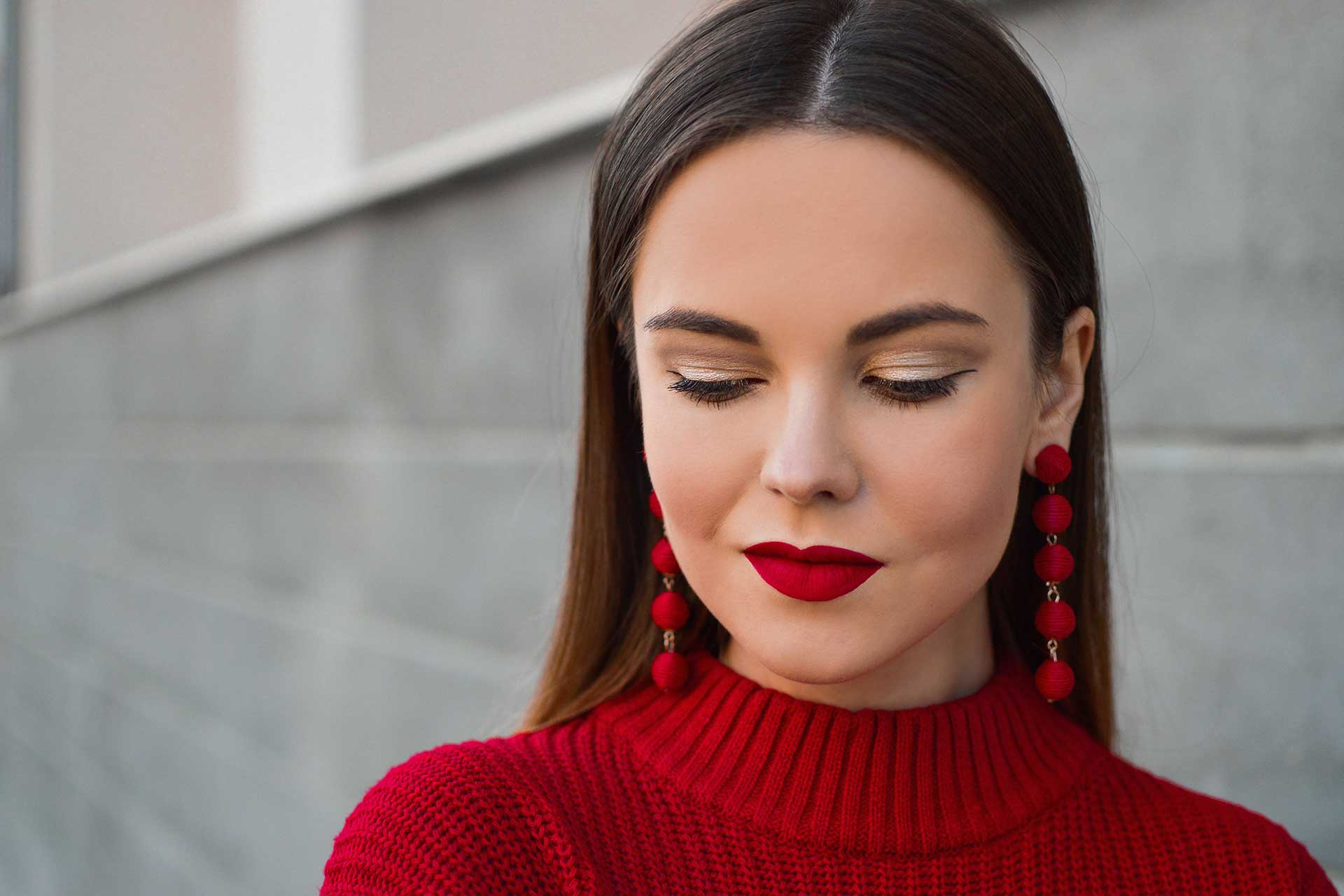 woman in a red sweater with sculpted eyebrows and lashes wearing red lipstick