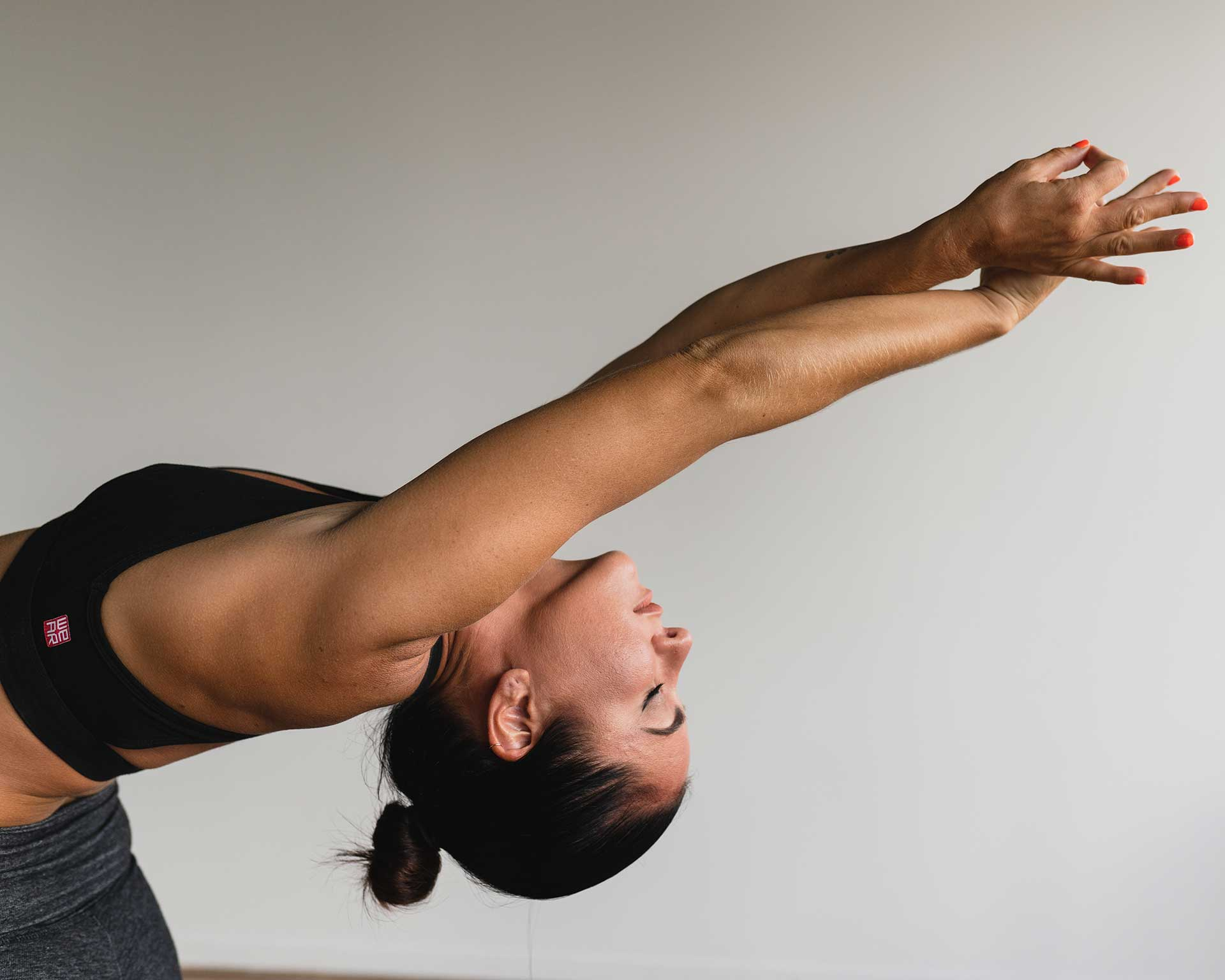 young woman bending backwards with arms overhead in yoga pose