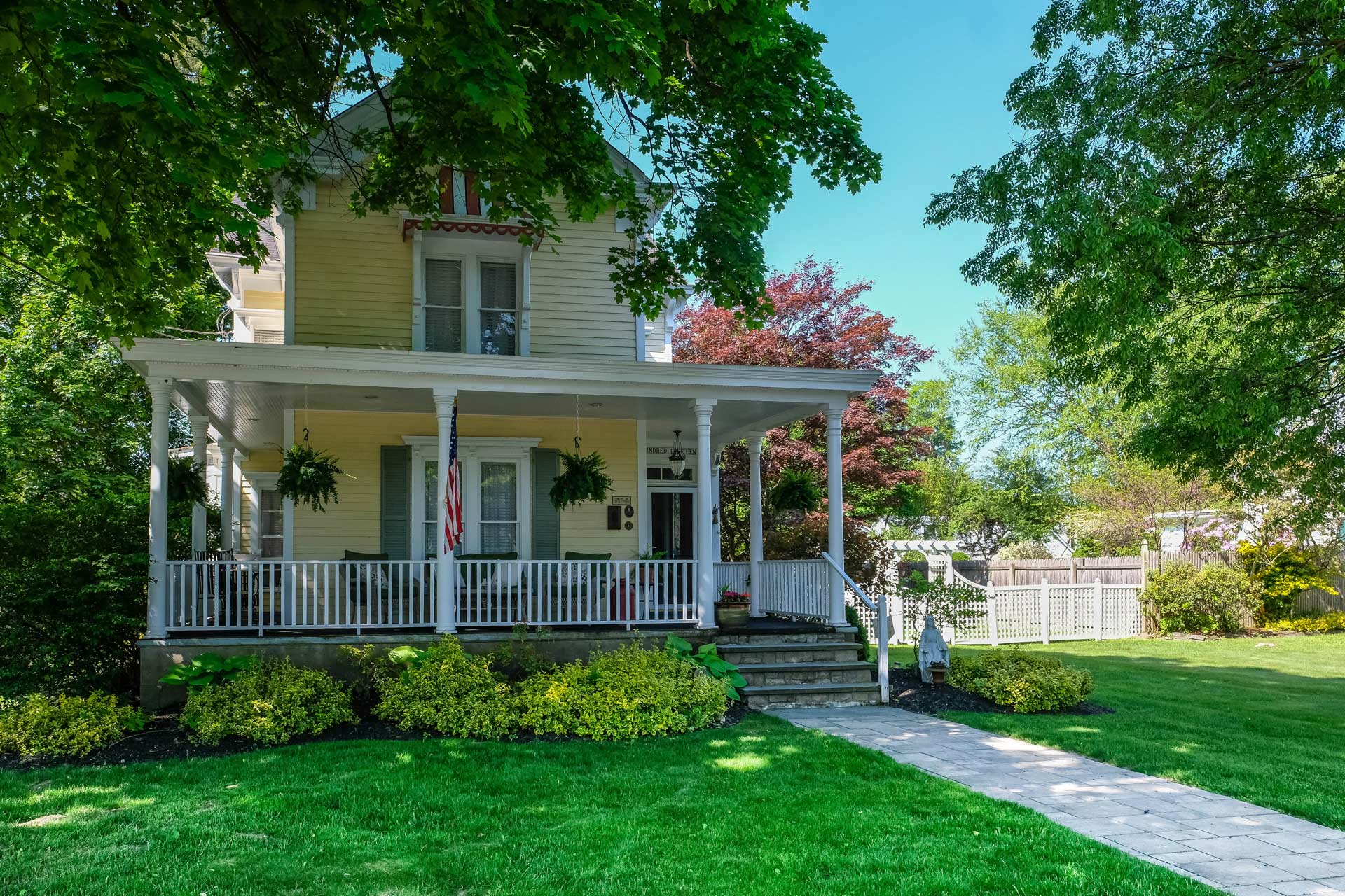 yellow house with wrap around porch and white trim and landscaping
