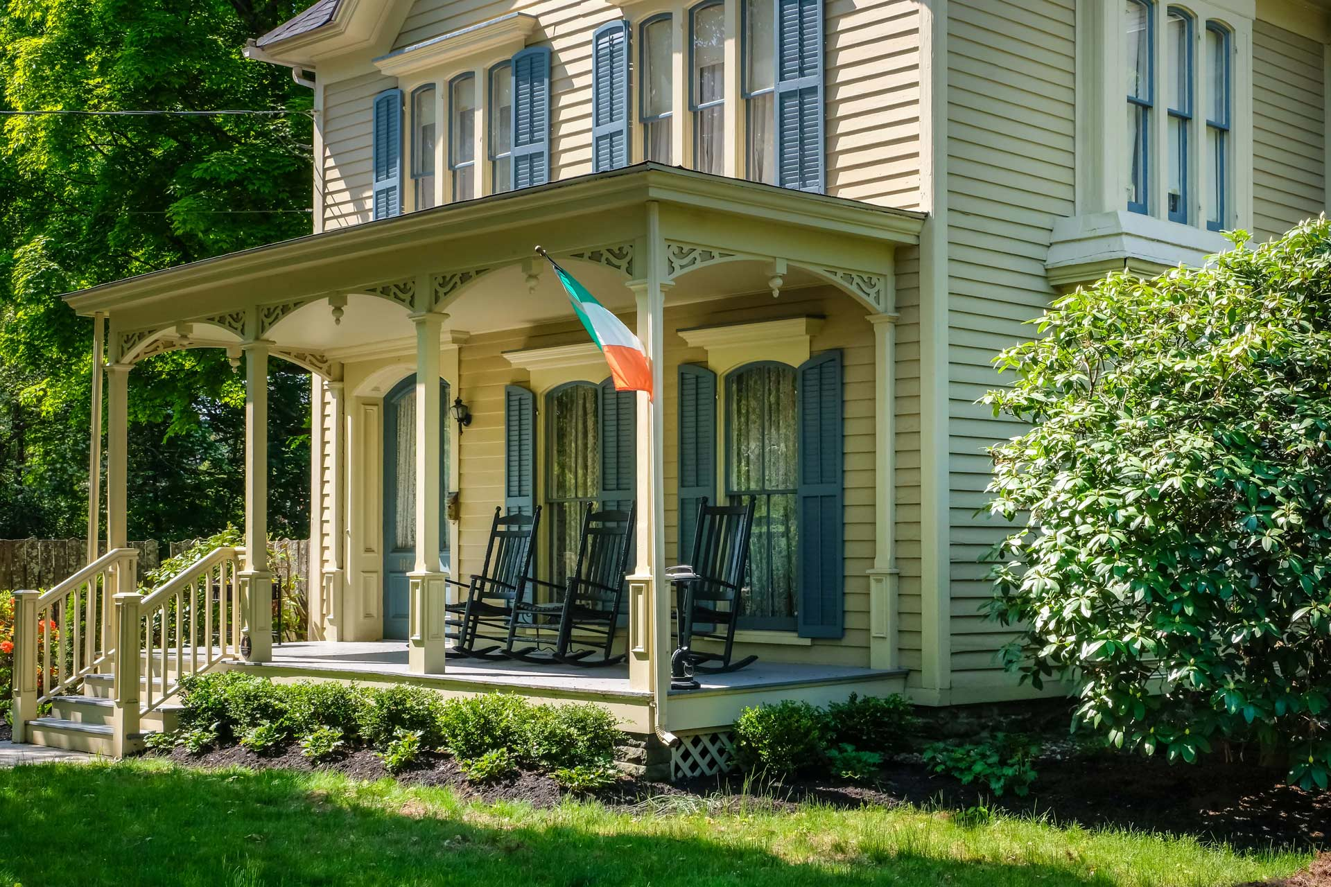 tan house with front porch and rocking chairs and irish flag