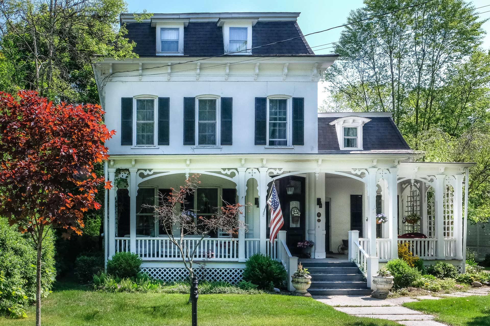 large old white house with black trim and large porch