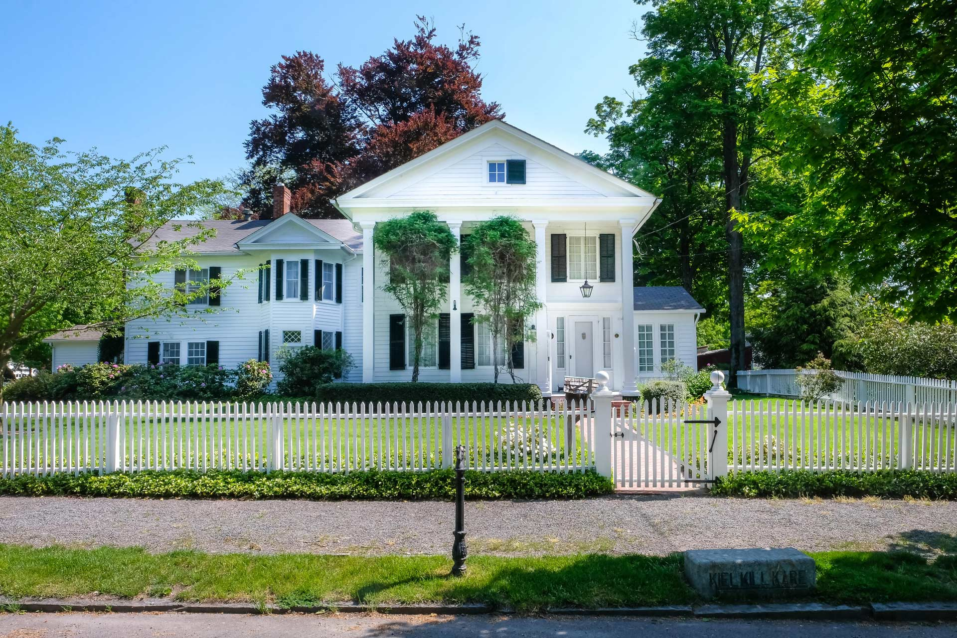 large old white house with black shutters and white picket fence
