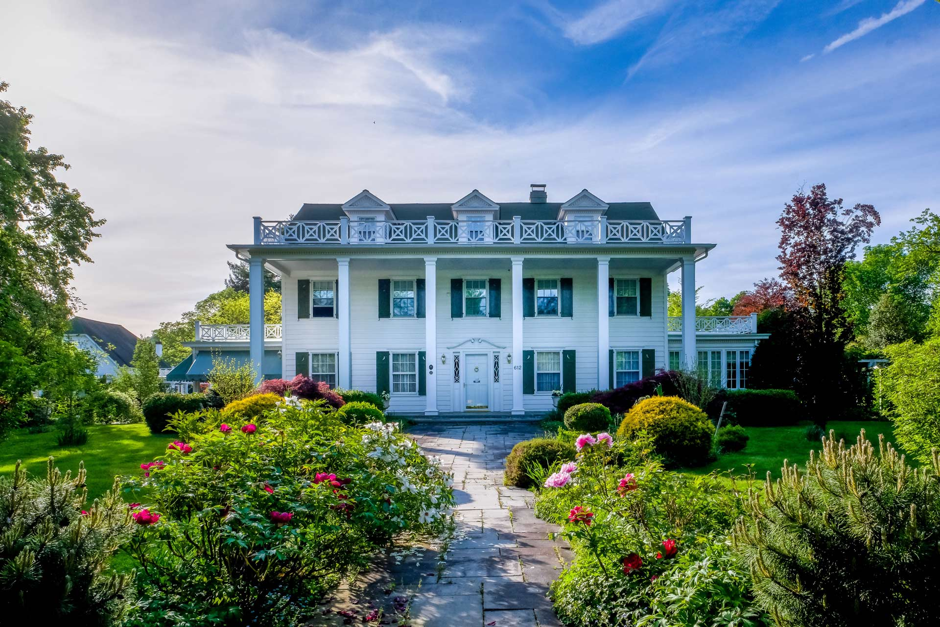 large 3 story white house with columns and large walkway with landscaping