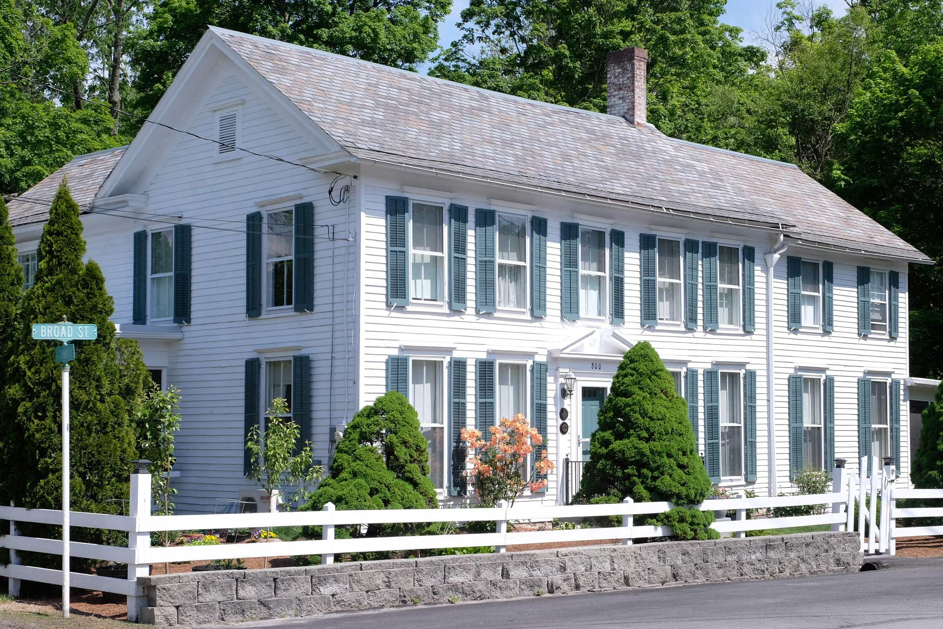large old white house with green trim and stone and white picket fence