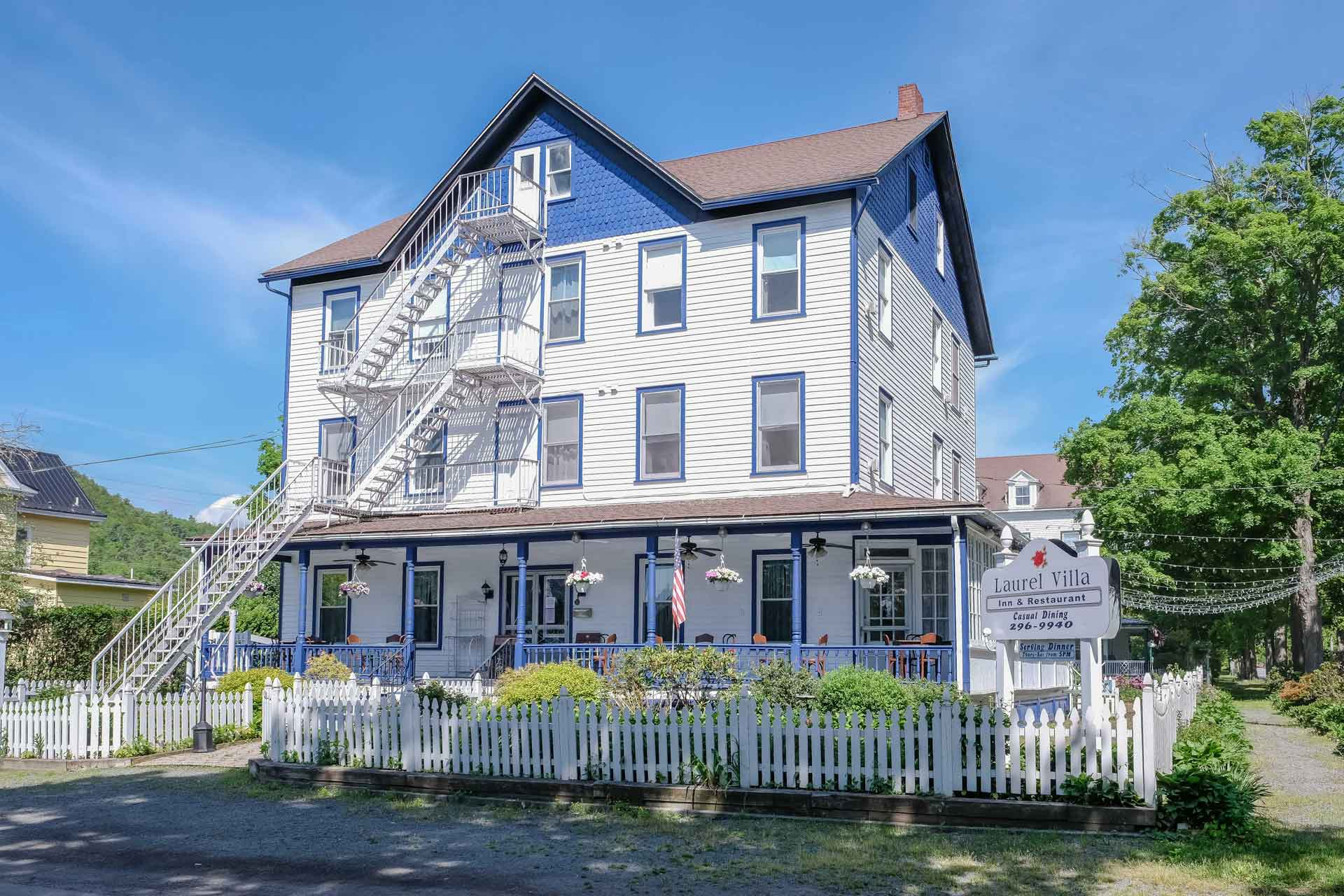 large historical white house with blue trim