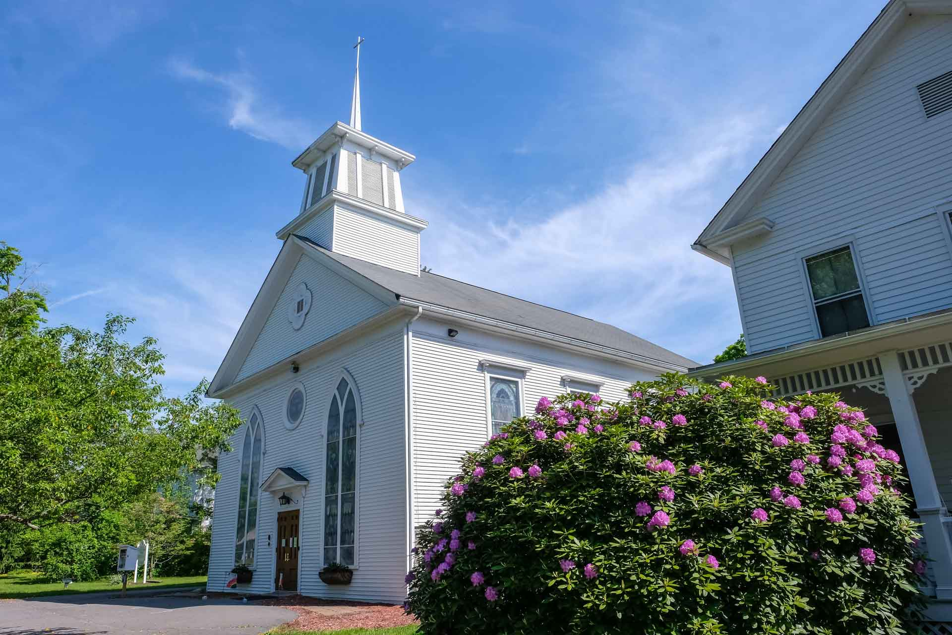 historical white methodist church with traditional stained glass windows and a steeple