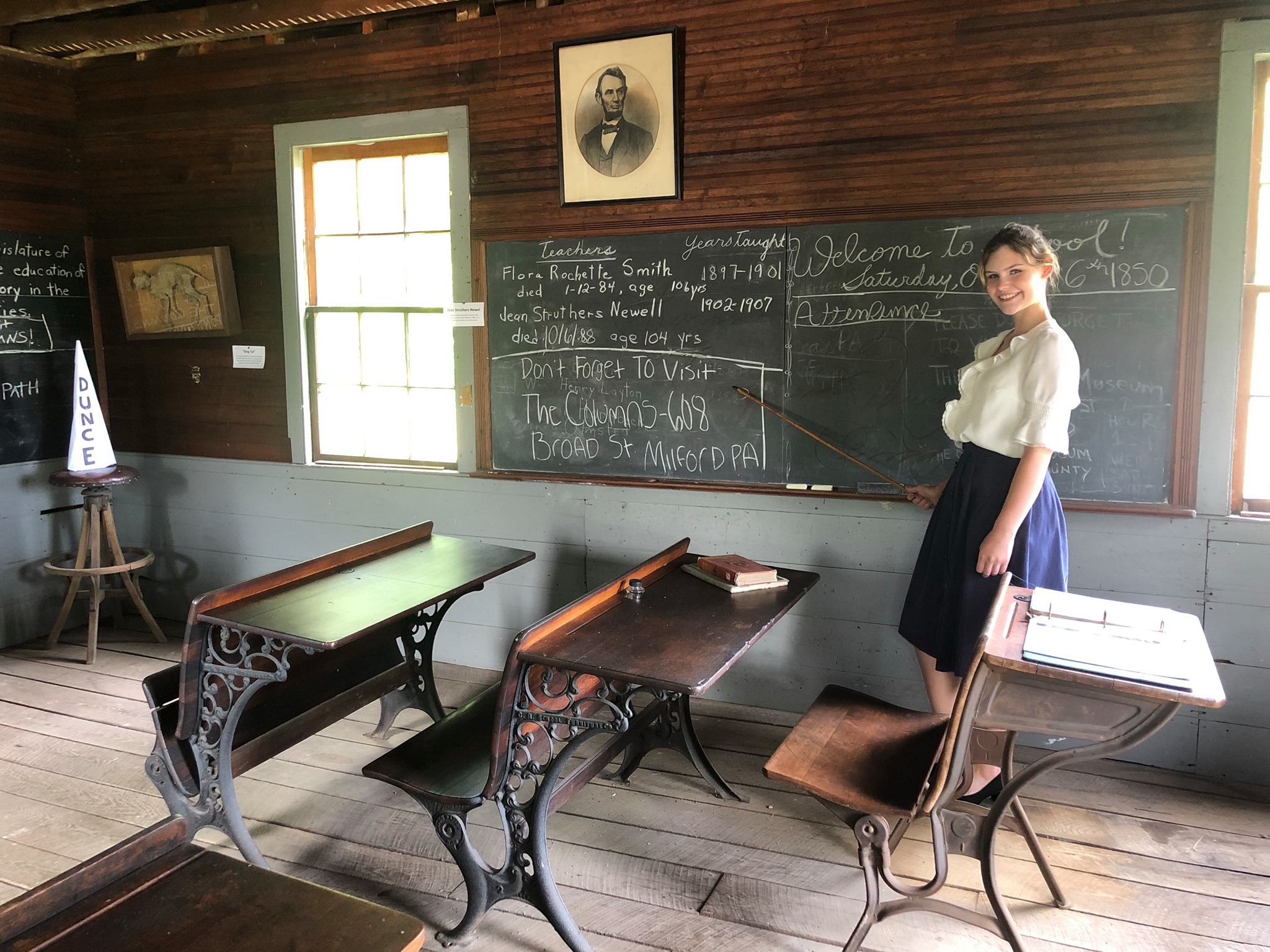 young female teacher recreating an old schoolhouse scene in the columns museum