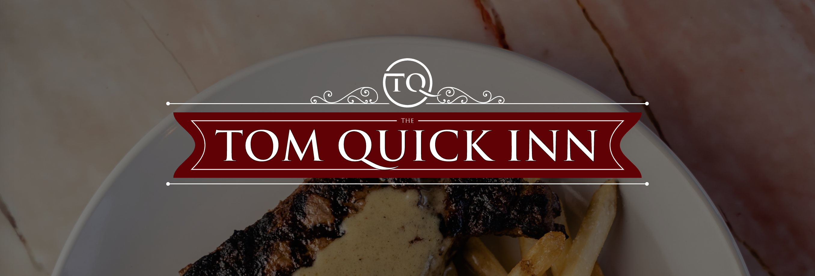 tom quick inn logo over a photo of a plated dinner