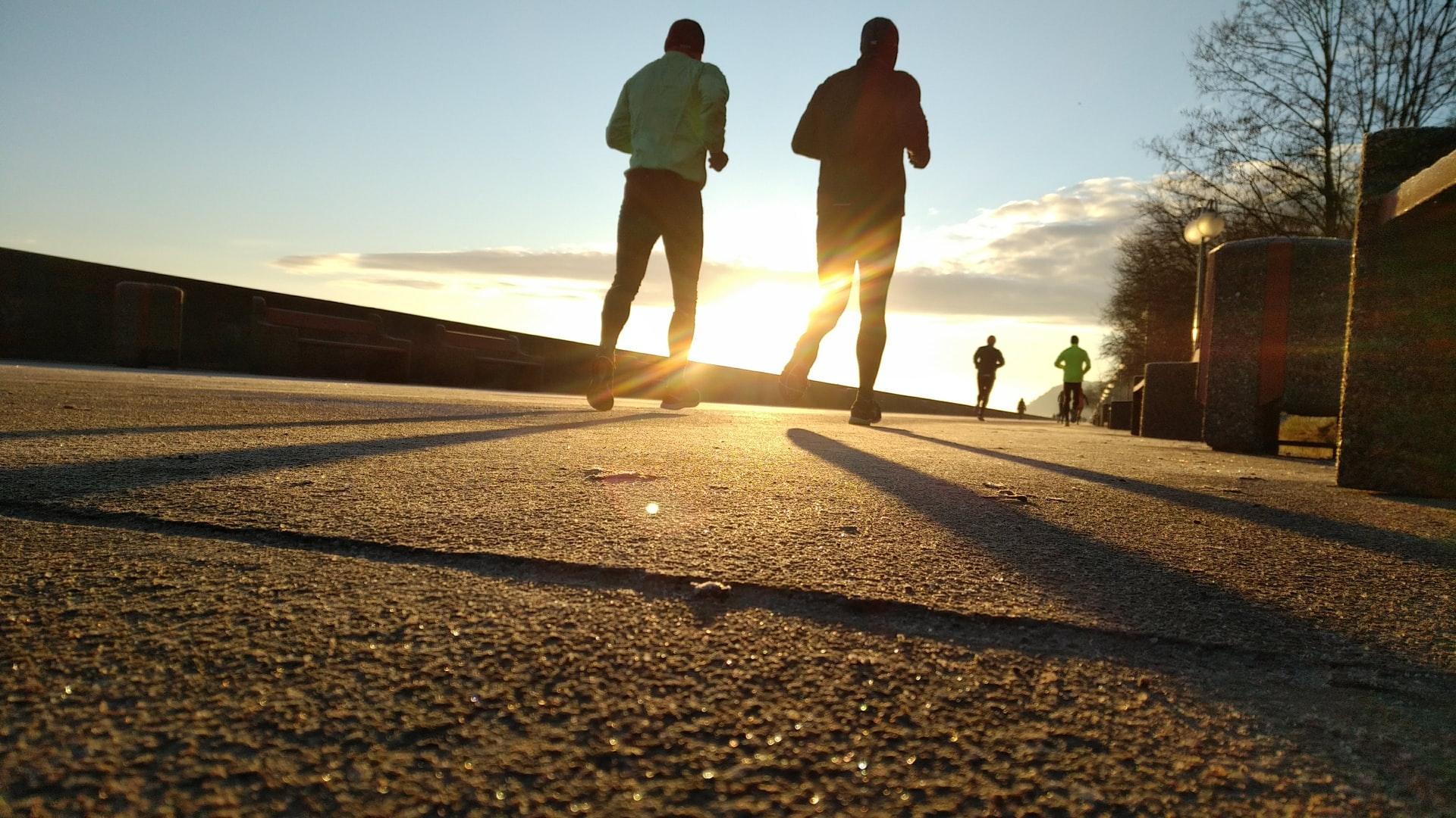 two men running during sun set