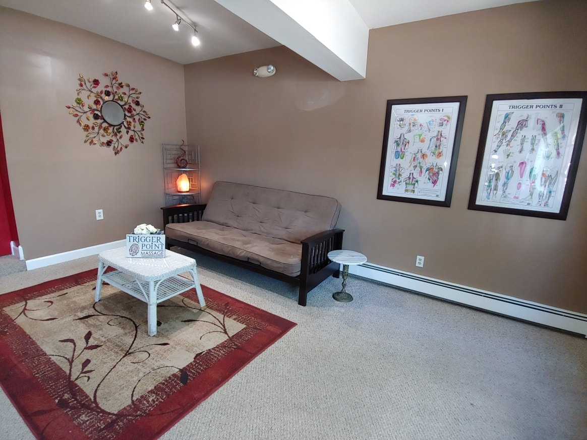a massage office waiting room area with a couch, table, and art on the walls