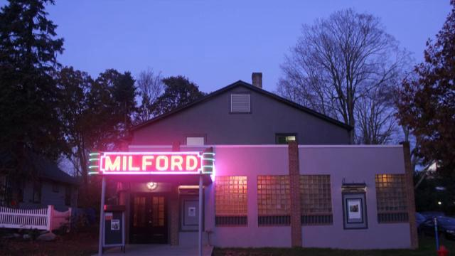 the outside of the milford theater at night with a lit sign reading milford over the door