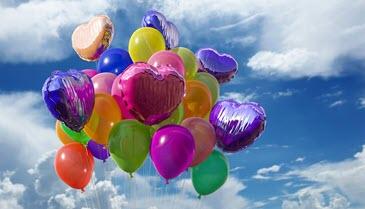 Floating balloons against sky.
