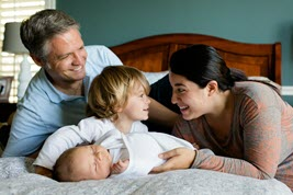 Family on bed with child.