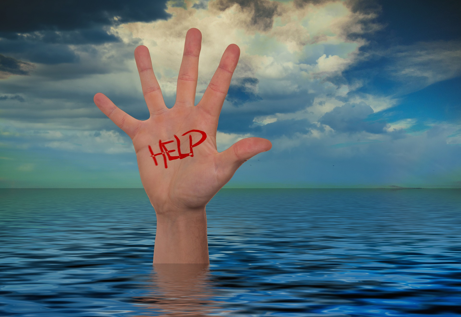 Hand Poking Through Water With 'Help' Written In Read To Signify A Disaster Recovery Plan