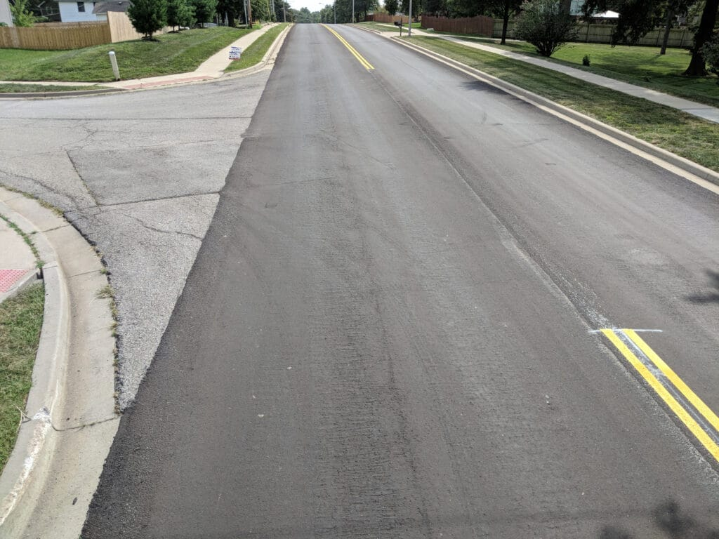road resurfaced with blacktop and new yellow stripes