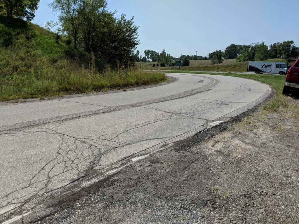 road with major alligator cracks next to a highway