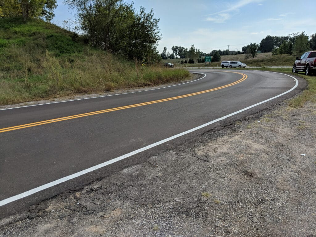 recently paved road next to a highway with double solid yellow striping