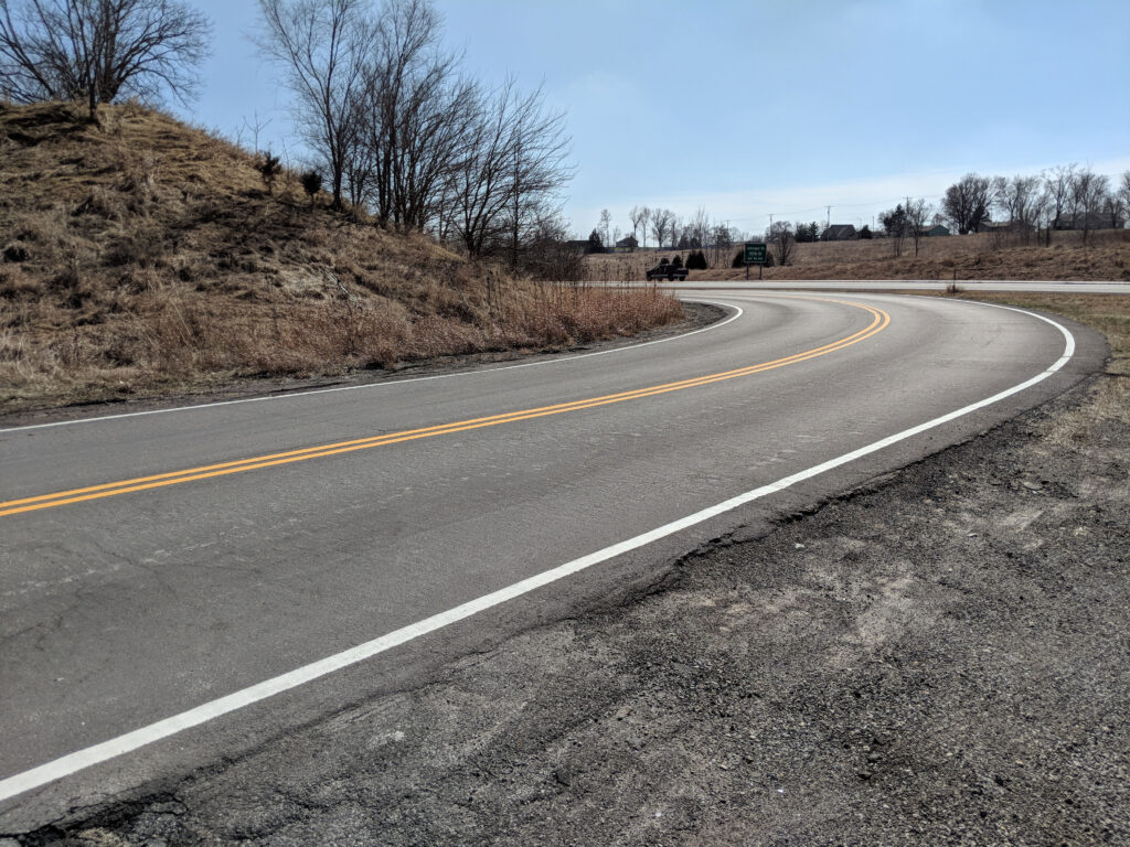 road next to a hill and highway after winter