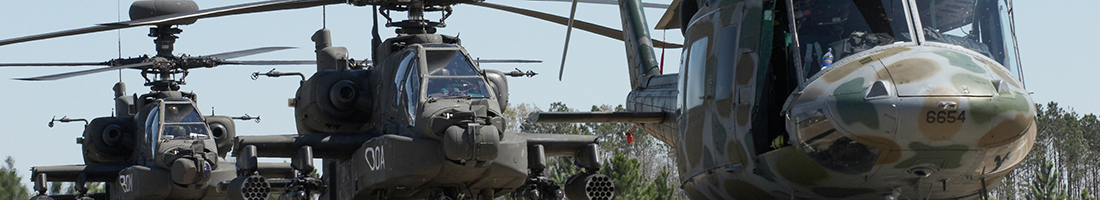 A set of three Apache helicopters sit on the helipad