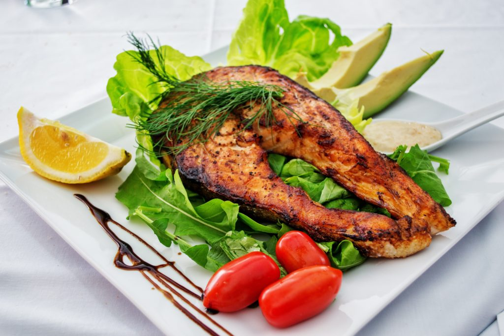 tuna steak over lettuce on white plate with fresh avocado and tomatoes and lemon