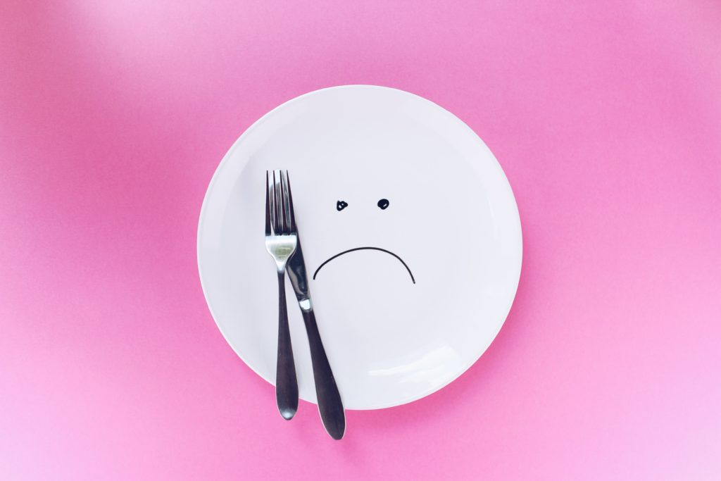 fork and knife lying next to frowning face drawn with black ink on empty white plate sitting on pink background