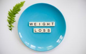green fern next to blue plate with scrabble letters spelling out weight loss