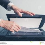 Man placing a piece of paper face down on a scanner bed