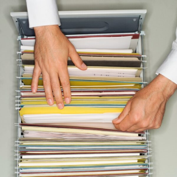 To hands filing a document in a set of file folders