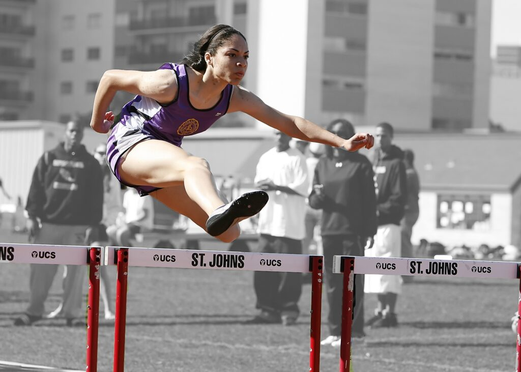 Woman running and jumping a hurdle
