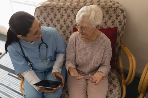 High angle view of female doctor discussing medical report with senior woman on digital tablet at home