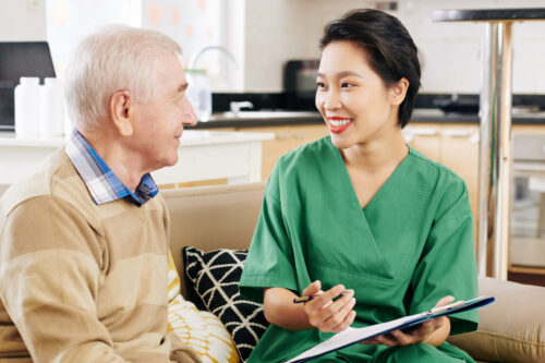 Young cheerful hospital worker visiting elderly patient at home and explaining him details in document with medical prescription