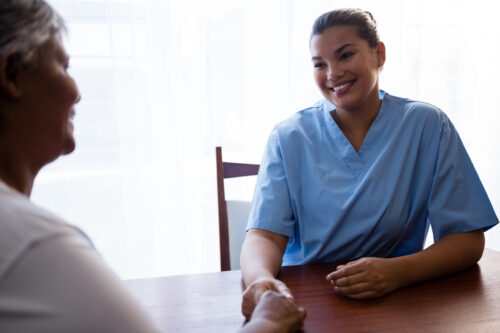 Nurse interacting with senior woman at table in retirement home