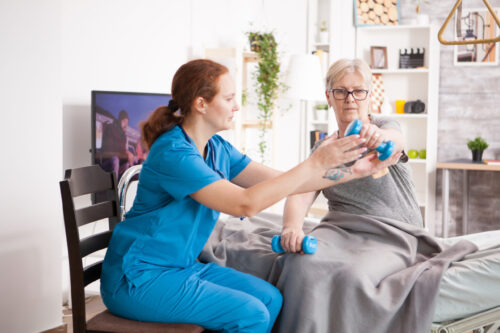 Senior woman in nursing home doing medical rehab using dumbbells with help from nurse.