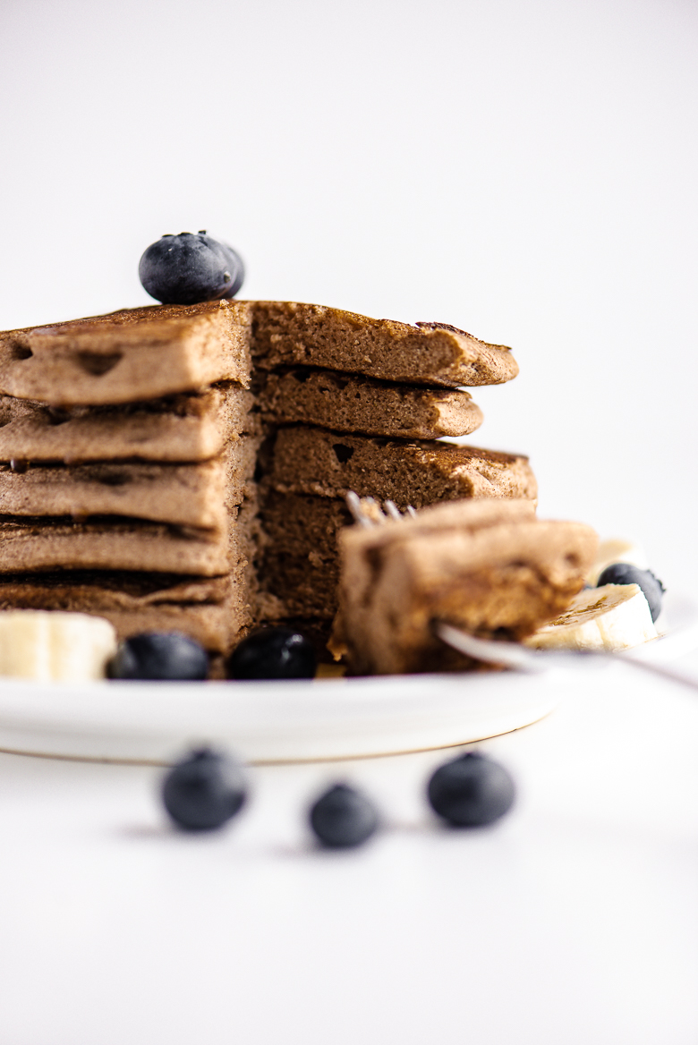 stack of vegan buckwheat flour pancakes, sliced on a plate with blueberries and banana slices