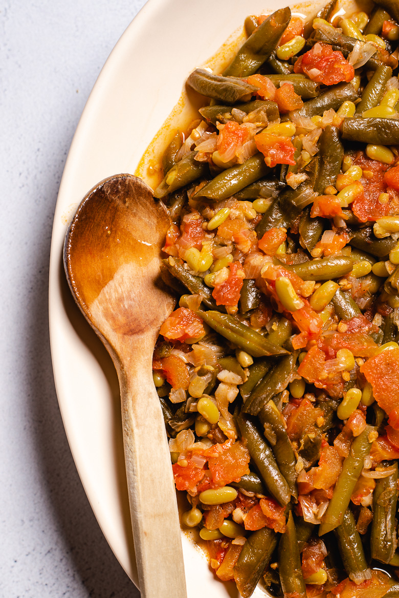 Turkish style stewed green beans on a plate with a wooden spoon - close up