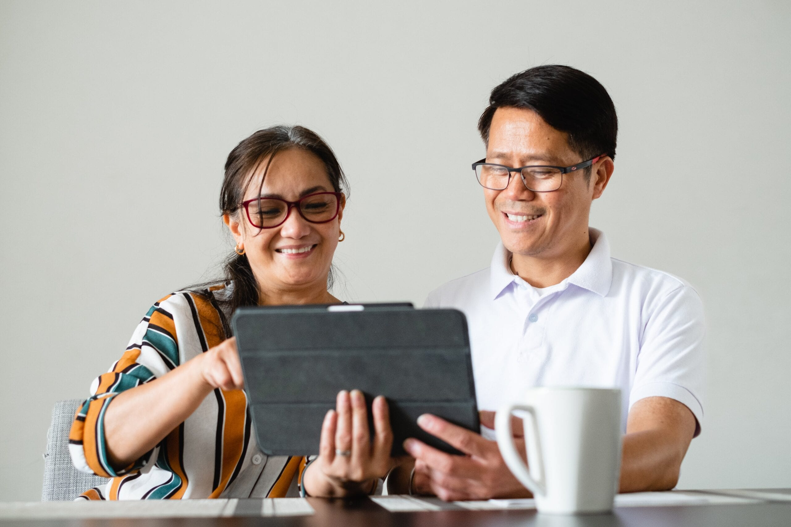 couple-smile-as-the-use-a-tablet