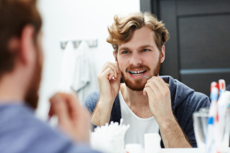 man flossing his teeth in the bathroom mirror