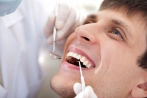 man getting his teeth examined for consultation on restorative dental options