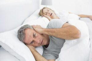 man lying in bed awake from wife's snoring and wishing she would get some sleep dentistry therapy