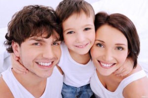 A family of 3 smile with healthy oral hygiene from good preventative dental therapy