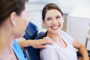 Woman smiling in dentist chair because of the great dental services she receives.