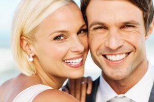 Couple smiling with beautiful smiles from teeth whitening cosmetic dental therapy