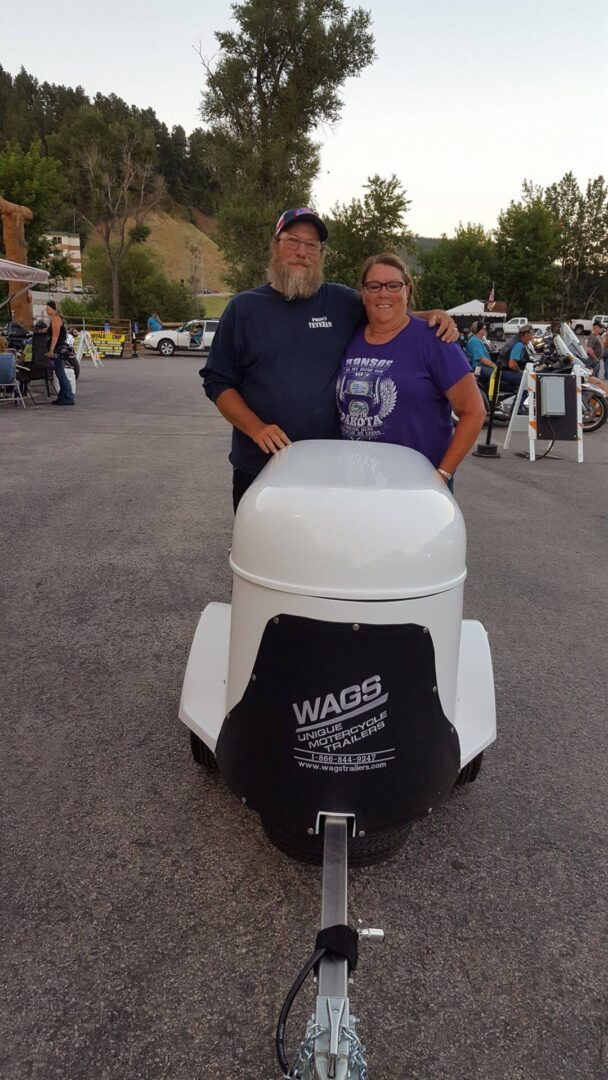 A couple holding a white pet trailer