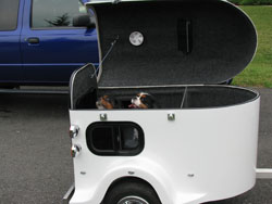 A white cargo trailer with two dogs inside