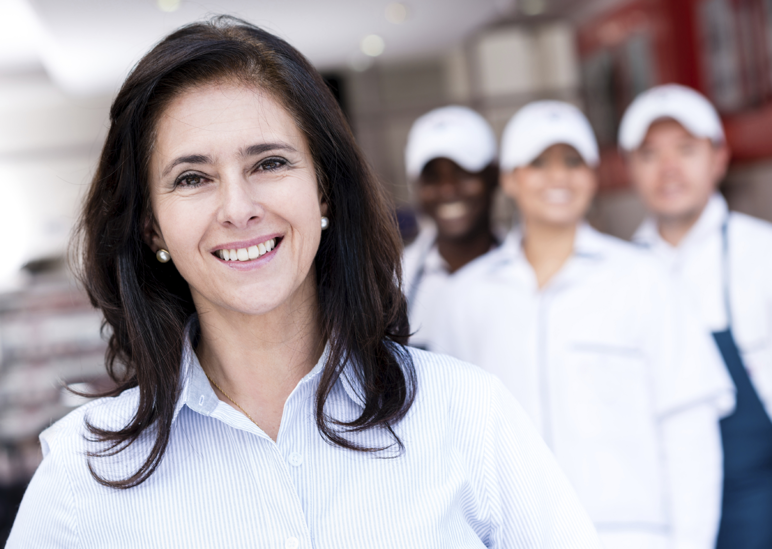 Portrait of a business owner smiling with her workers in the background