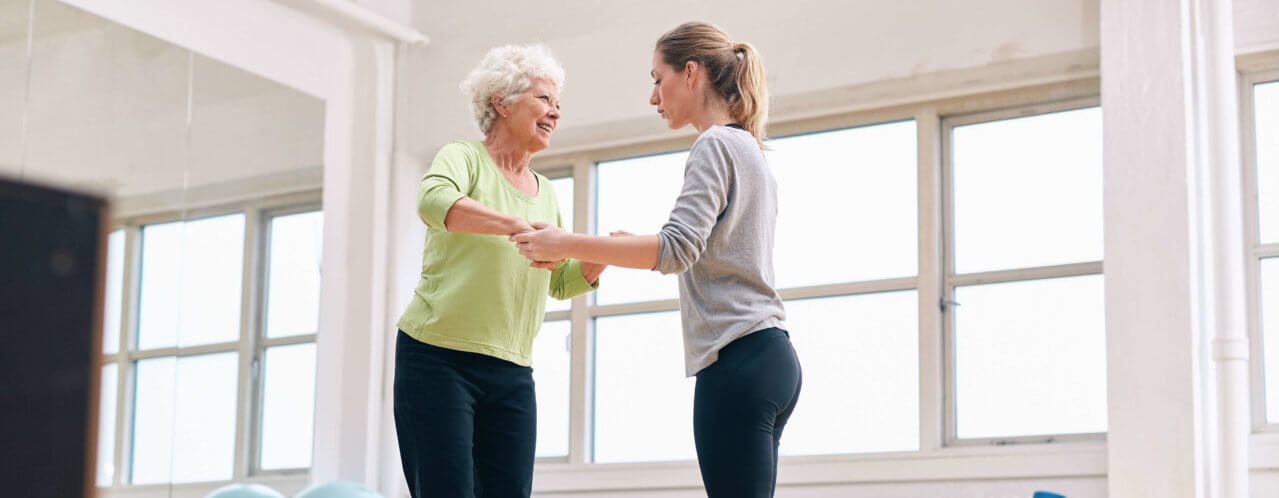 Trainer helping senior woman on bosu balance training platform