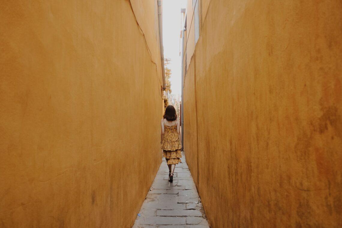 photo of woman walk through pathway