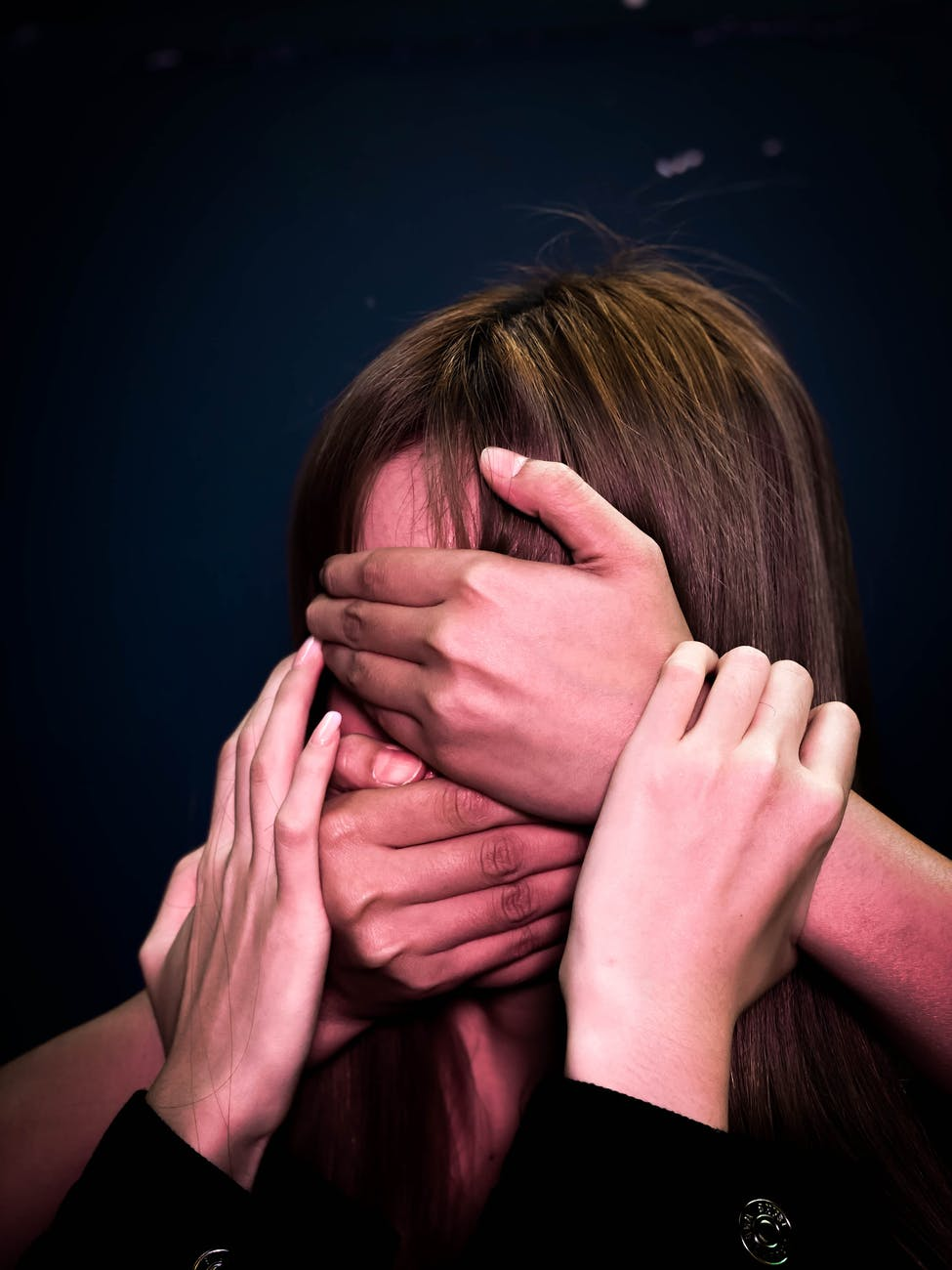 people covering face and mouth of helpless woman