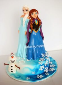 beautiful elsa and anna figurines on cake